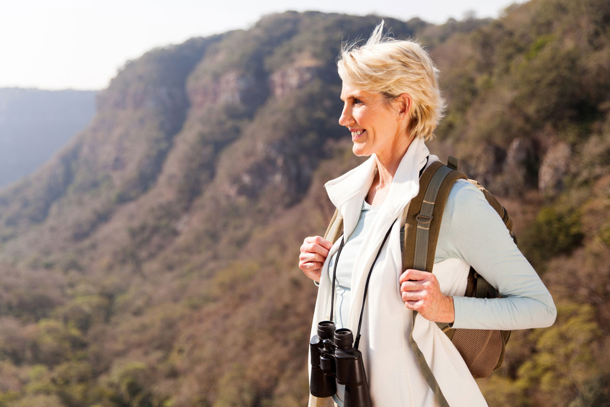 woman on a mountain with a backpack and binoculars